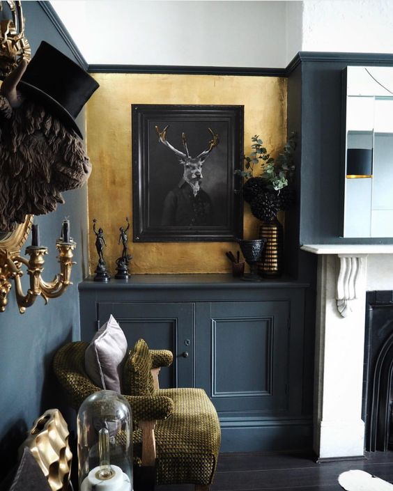 a modern and bright Gothic liivng room with grey and gold walls, a fireplace, grey paneling, gold touches and artworks