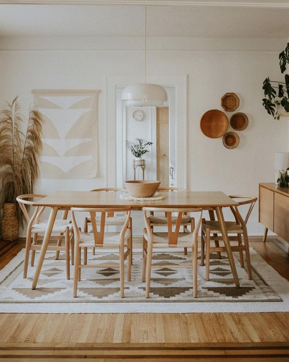a modern boho dining space in neutrals, with a wooden dining set, printed textiles, decorative baskets and pampas grass