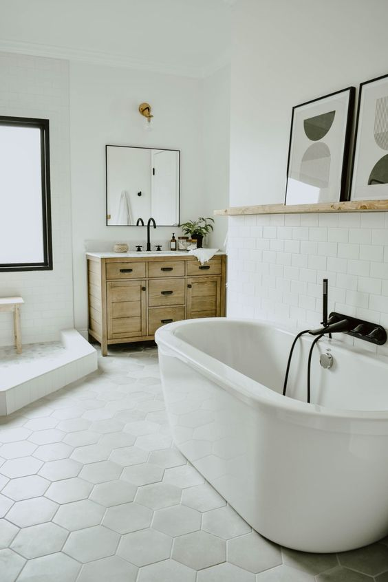 a modern eclectic bathroom with a hex tile floor, an oval tub, a wooden vanity, black fixtures and a ledge with artworks