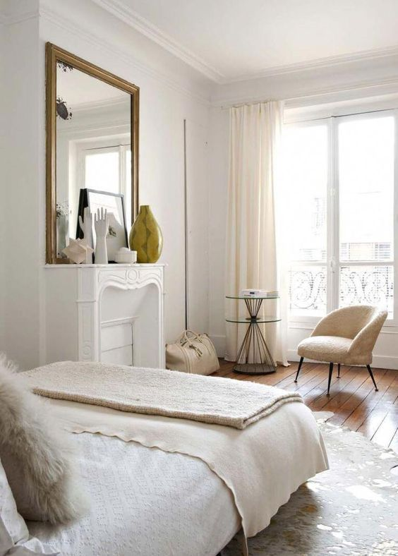 a neutral Parisian bedroom with a non working fireplace, neutral furniture and linens and pretty artworks