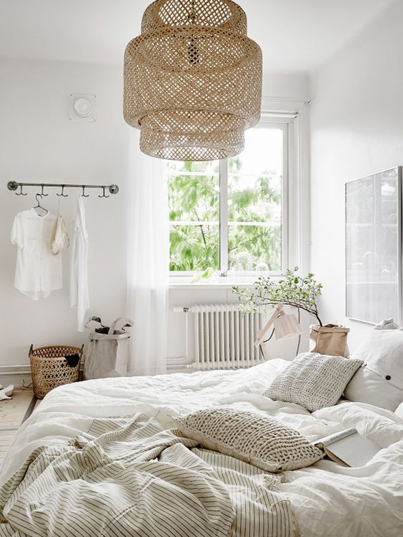 a neutral Scandinavian bedroom with white furniture, a pendant woven lamp, neutral bedding and some greenery