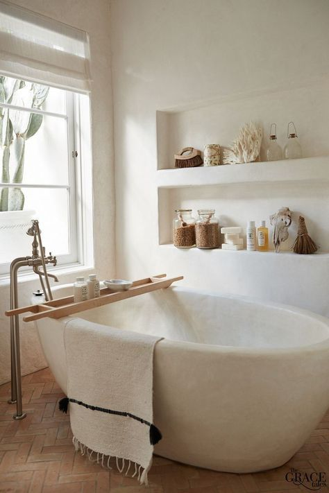 a neutral and welcoming bathroom with built-in shelves, an oval tub carved of stone and touches of wood