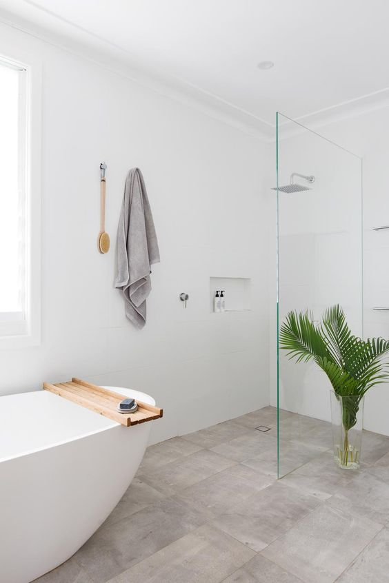 a neutral bathroom clad with tan tiles, an oval tub, neutral textiles and leaves in a vase and an airy glass divider