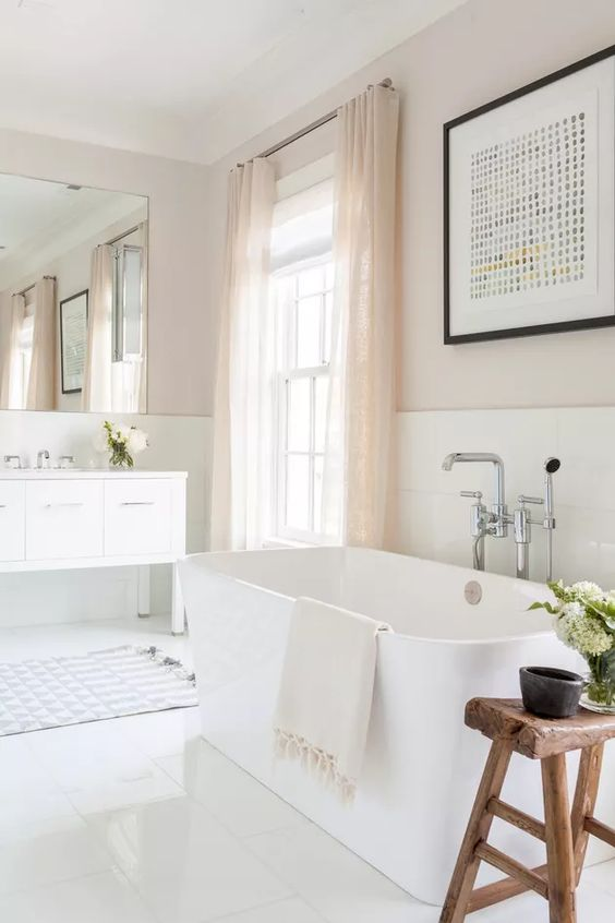 a neutral bathroom with a white vanity and an oval tub, a wooden stool, blush curtains and a bold graphic artwork