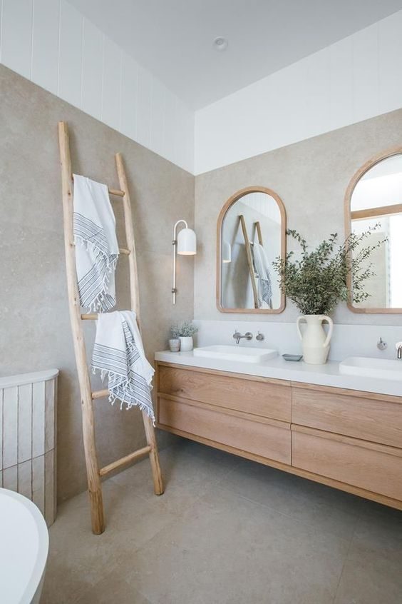 a neutral bathroom with a wooden floating vanity, arched mirrors in wooden frames, a ladder and neutral textiles