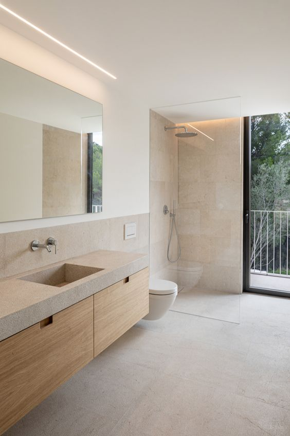 a neutral bathroom with a wooden vanity with a concrete countertop, neutral tiles and a narrow and long window is amazing