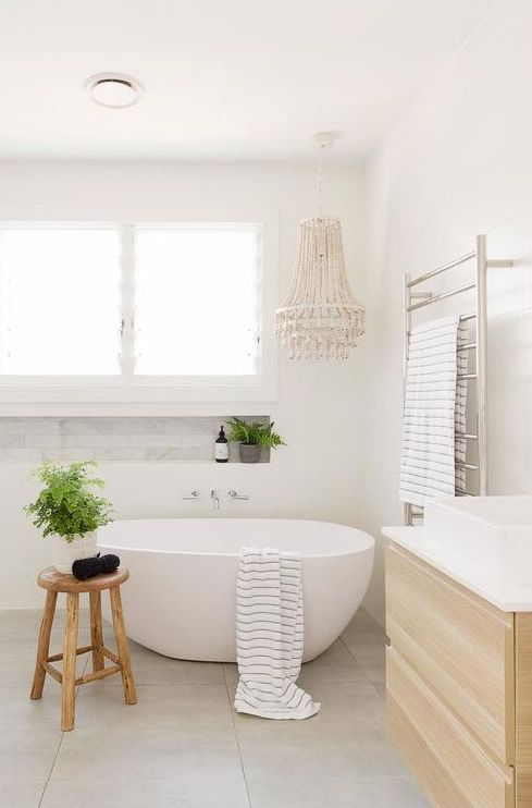 a neutral bathroom with an oval tub, a floating wooden vanity, a beaded chandelier, potted plants and a wooden stool