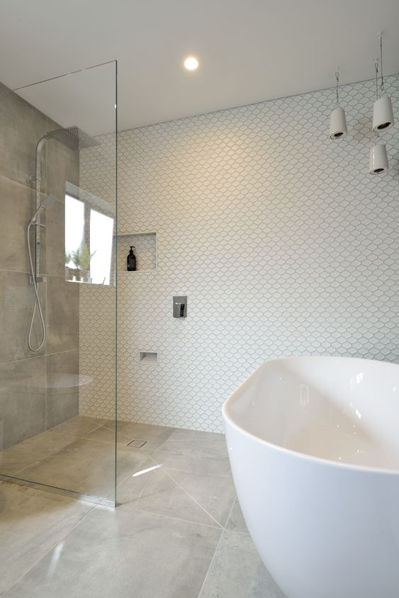 a neutral bathroom with mismatching tiles, an oval tub, a grey tile accent wall, pendant porcelain pendant lamps