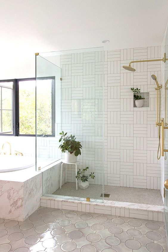 a neutral bathroom with mismatching tiles, potted greenery and gold fixtures is a stylish idea with a modern feel