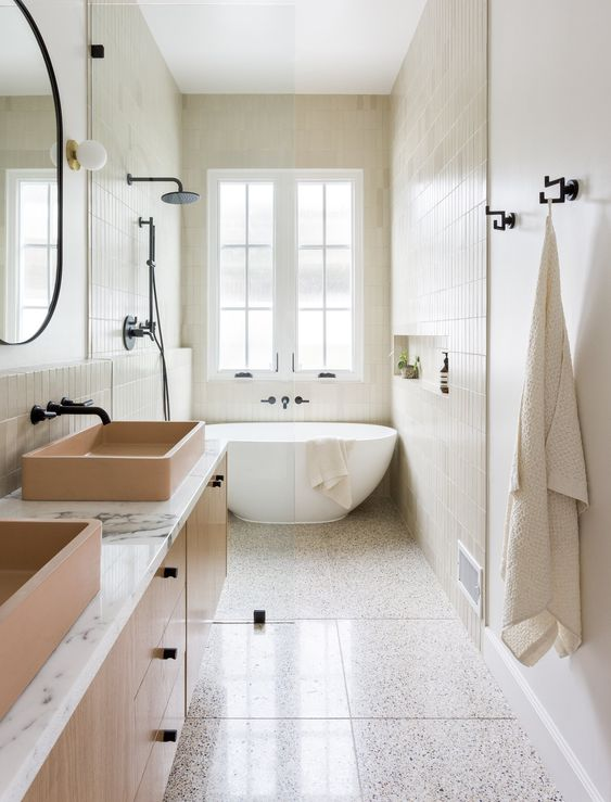 a neutral bathroom with tiles cladding the walls and floor, an oval tub, a floating vanity with tan sinks and black fixtures