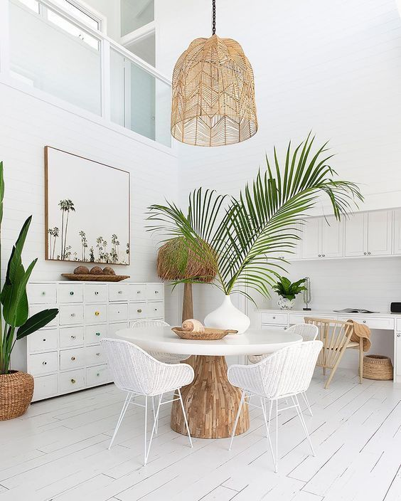 a neutral beachy dining room with a dress, a round table, a woven lamp, white woven chairs, potted plants  and some beachy artworks