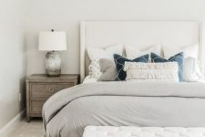 a neutral bedroom with a creamy bed, a white upholstered bench, wooden nightstands and printed pillows