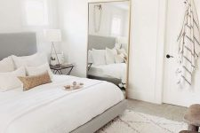 a neutral bedroom with a grey upholstered bed, an oversized mirror, a pendant lamp and printed pillows