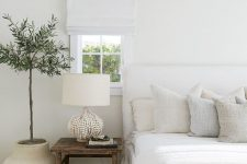 a neutral bedroom with a white upholstered bed, neutral pillows, a white lamp and white shades plus a statement plant