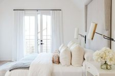 a neutral bedroom with an upholstered bed, neutral bedding, a printed rug and a chic retro chandelier