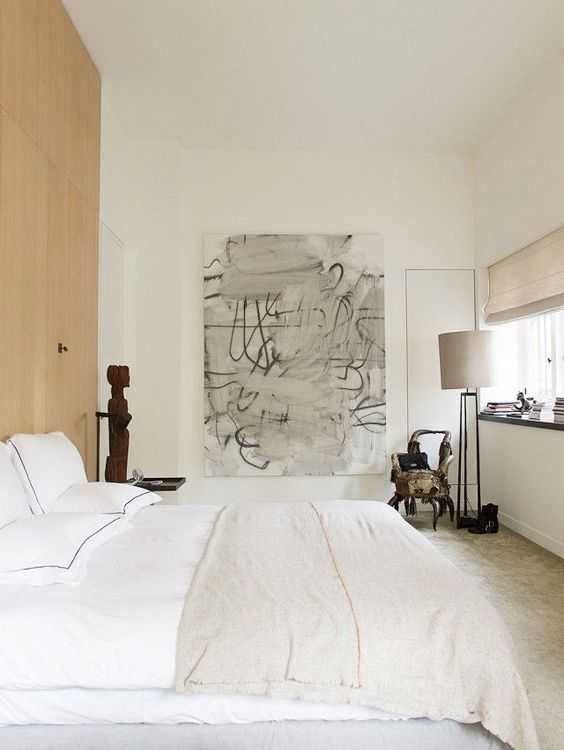 a neutral bedroom with light colored furniture and lamps, with a wooden accent wall and some bold and dramatic art
