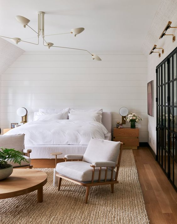 a neutral bedroom with white beadboard, a white bed and a chair, a wooden round table and some blooms and greenery