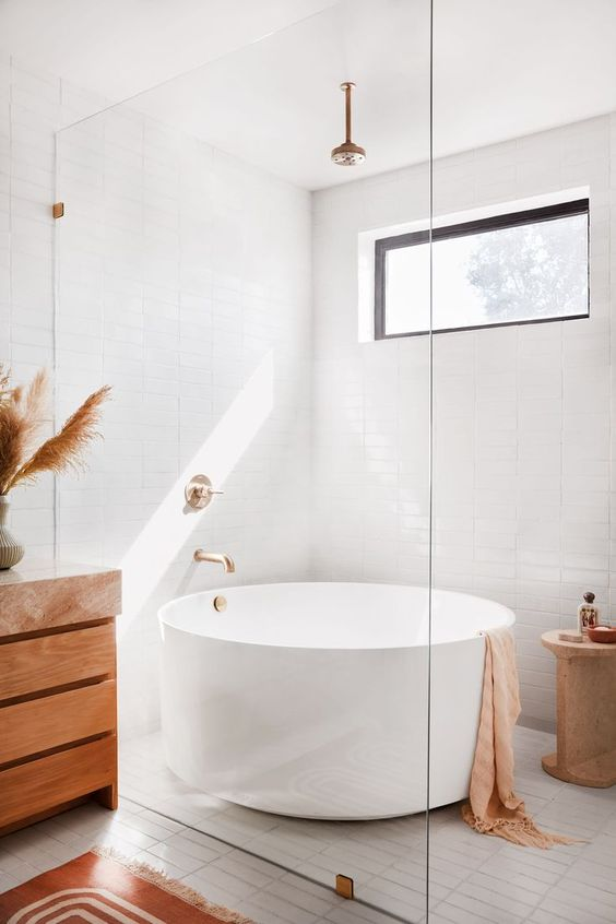 a neutral boho bathroom with a window, a round bathtub, a wooden vanity, pampas grass, a wooden side table and tan textiles