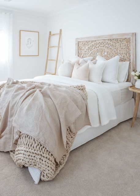a neutral boho bedroom with a carved wooden bed, a ladder, neutral and tan bedding and a wooden nightstand