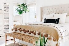 a neutral boho bedroom with a creamy bed, a woven bench, boho hangings, statement plants and tassel blankets