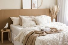 a neutral boho bedroom with a terracotta accent, a pendant lamp, woven baskets, layered bedding