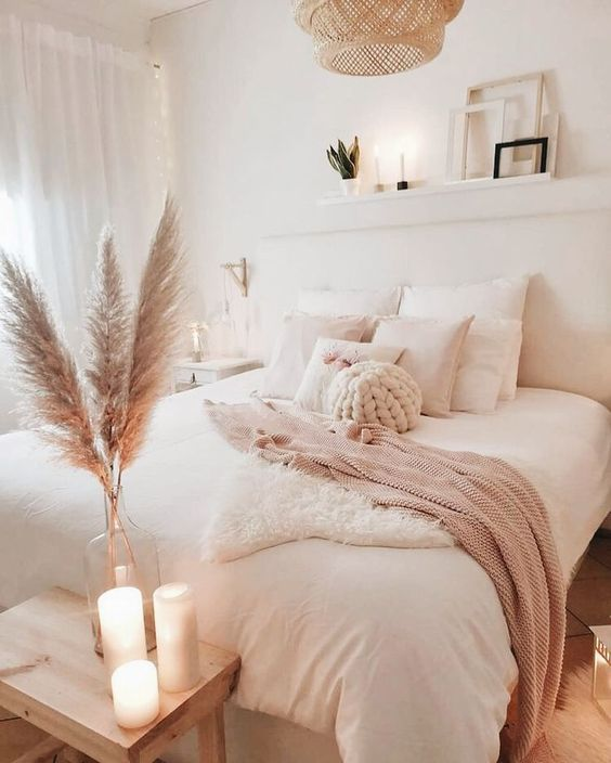a neutral boho bedroom with white furniture, a woven lamp, pampas grass and candles