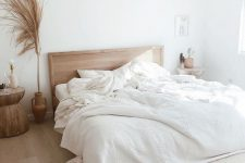 a neutral boho bedroom with wooden furniture and a woven lamp, with pampas grass and neutral bedding is an oasis