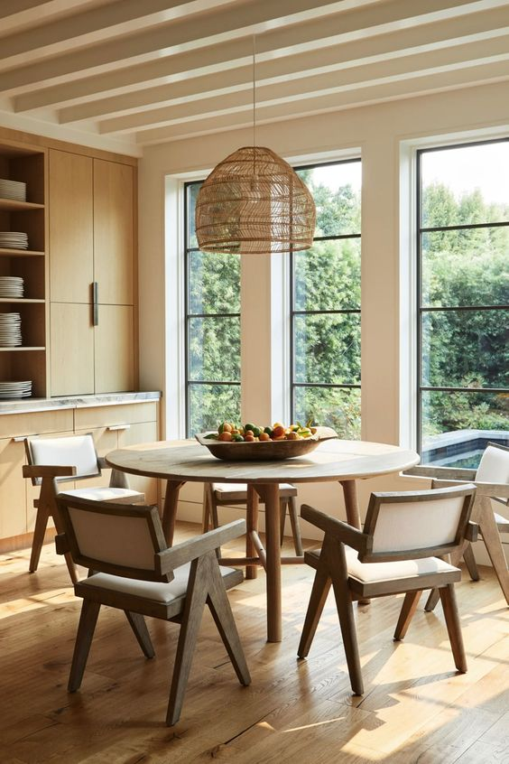 a neutral chic dining room with sleek stained storage units, a round table, some elegant chairs and a woven pendant lamp plus a gorgeous view