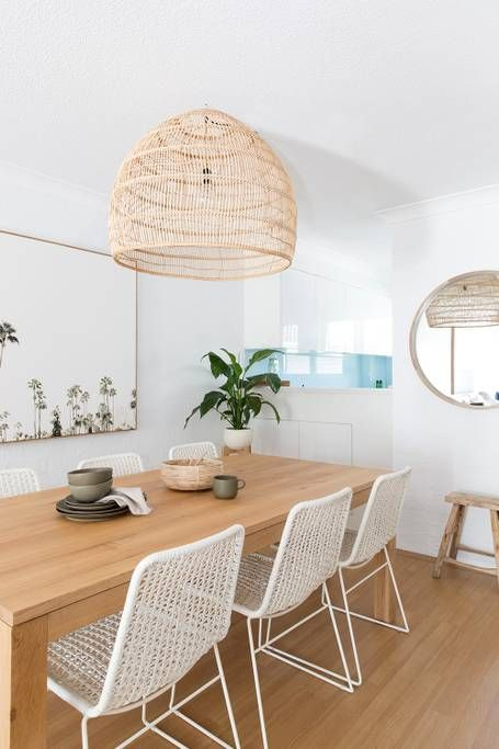 a neutral coastal dining room with a stained table, woven chairs, a lovely woven lamp and a round mirror plus some beach art