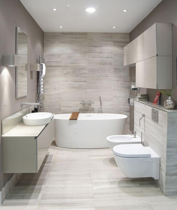 a neutral contemporary bathroom clad with grey tiles, with white appliances and a floating vanity plus built-in lights