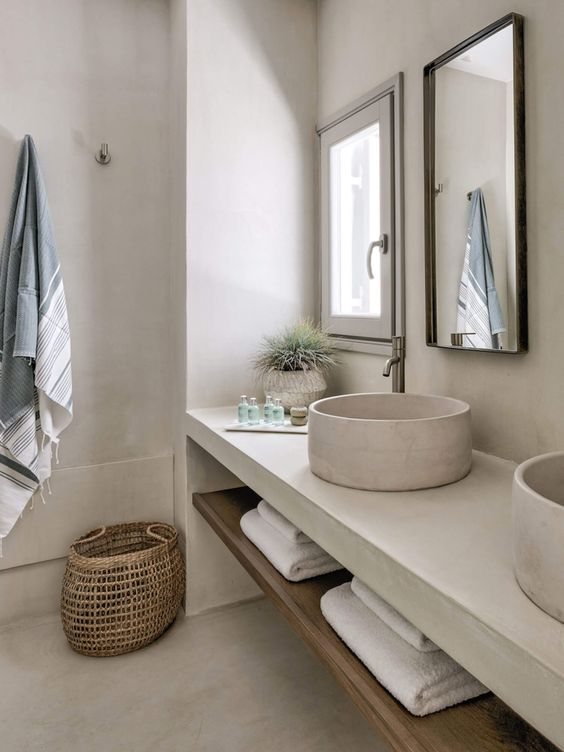 a neutral contemporary bathroom clad with white concrete, with a white concrete vanity and sinks, a basket and neutral textiles