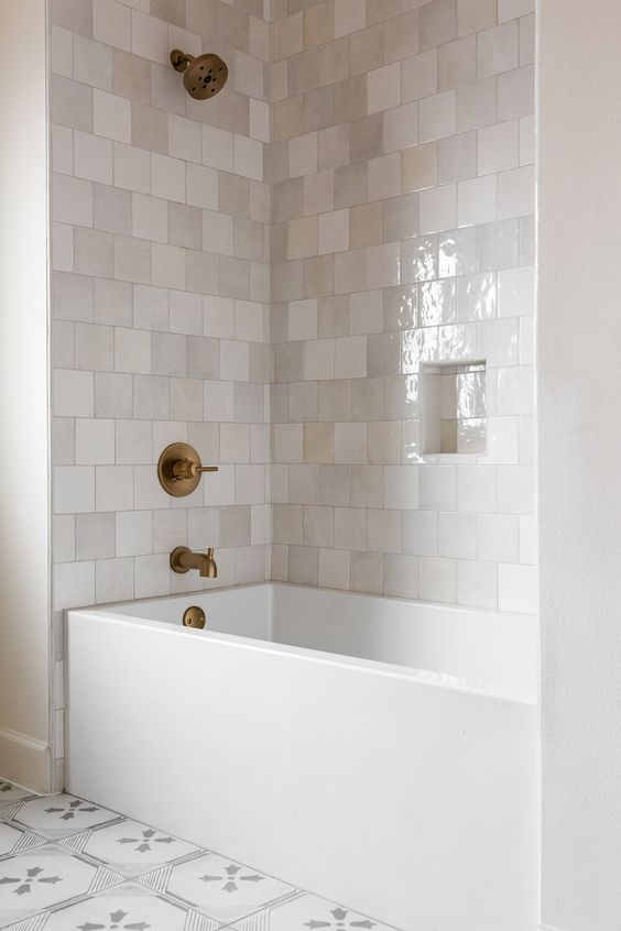 a neutral contemporary bathroom with glossy neutral tiles, a rectangular tub, printed tiles and brass fixtures for a refined look