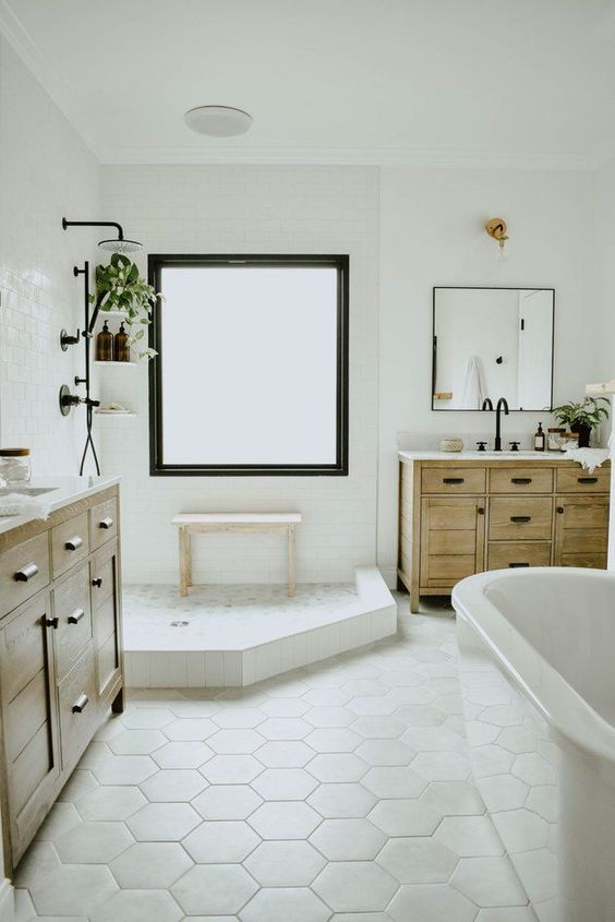 a neutral farmhouse bathroom with a two wooden vanities, an oval tub, a shower space with a large window with frosted glass