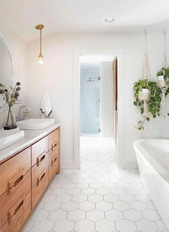 a neutral farmhouse bathroom with large scale hex tile,s a wooden vanity, an oval tub, white sinks and a pendant bulb