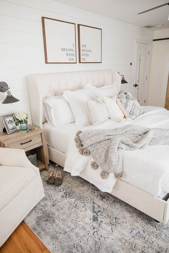 a neutral farmhouse bedroom with creamy furniture, artworks, neutral textiles and printed rugs and blankets