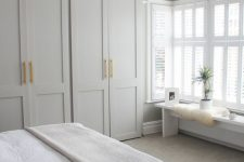 a neutral modern bedroom with ddove grey wardrobes, neutral furniture and a pendant lamp