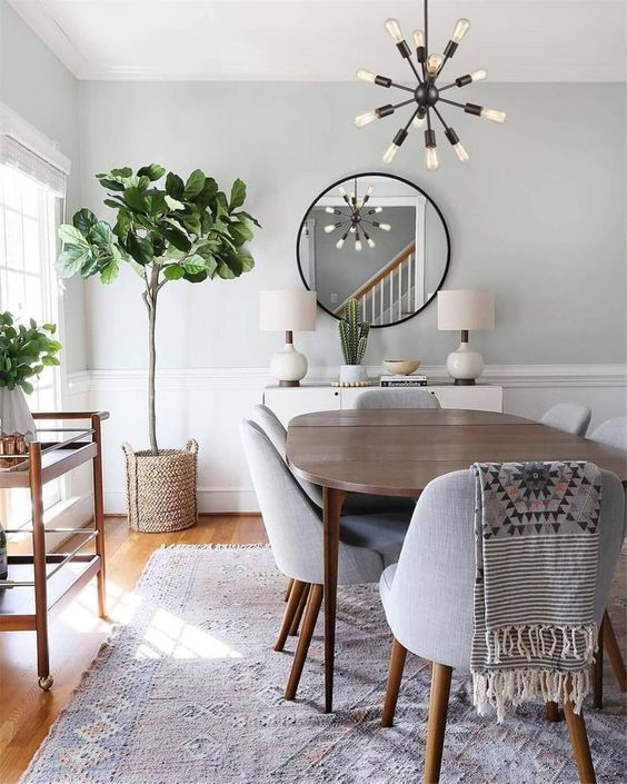 a neutral modern dining space with a stained wooden table, grey chirs, a bar cart, a round table, some potted greenery