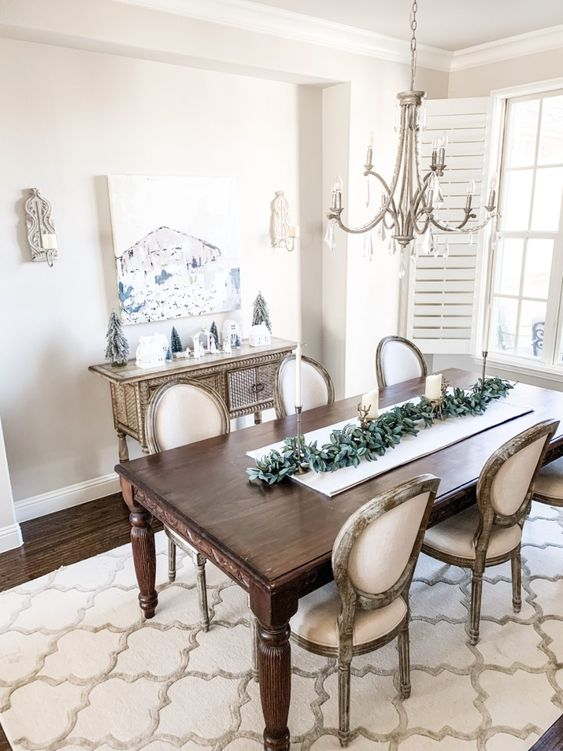 a neutral shabby chic dining room with an elegant inlay console, a dark stained table and chic chairs, a crystal chandelier