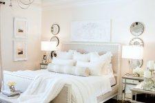 a neutral vintage bedroom with elegant furniture, decorative plates, a vintage chandelier and artworks