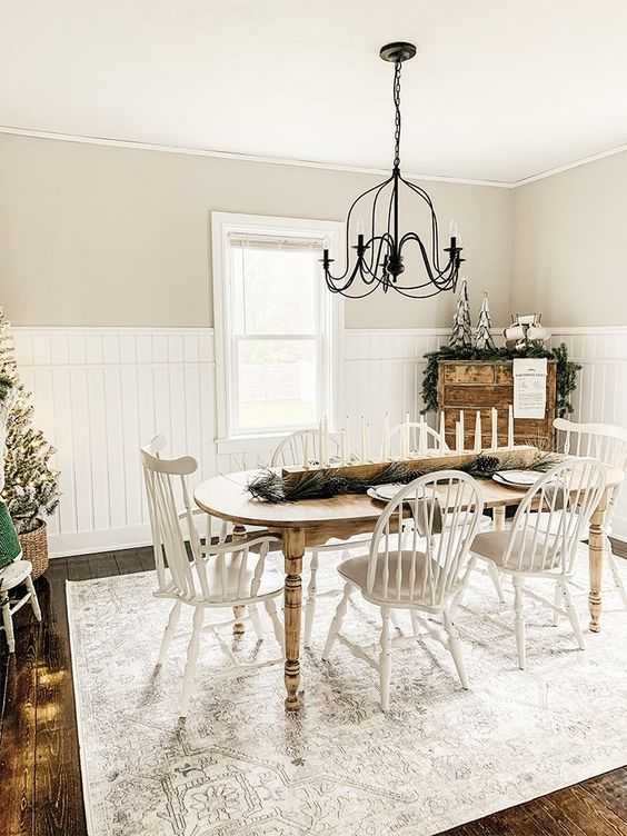 a neutral vintage farmhouse dining room with a curved table, white chairs, a metal chandelier and a wooden dresser