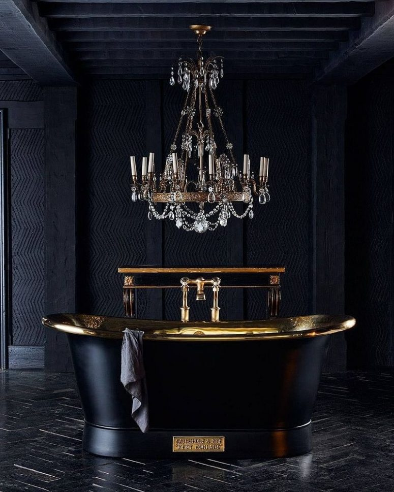 a refined Gothic bathroom with textural graphite grey walls, a black and gold polished bathtub, a crystal chandelier and a black parquet floor