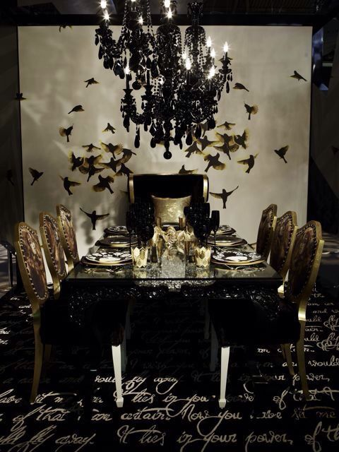 a refined Gothic dining room with a white accent wall with birds, a glass table, gold chairs, several black crystal chandeliers
