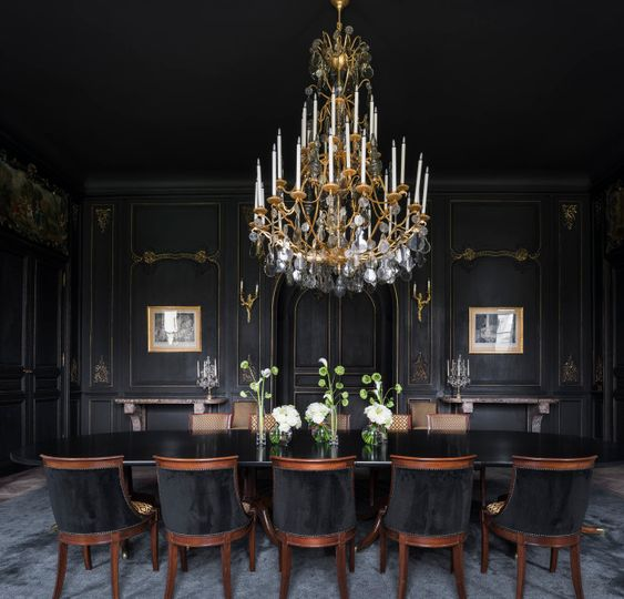 a refined Gothic dining room with black walls, a black table and chairs, artworks and a large crystal and gold chandelier