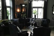 a refined Gothic space with elegant black furniture, a black chandelier and potted greenery