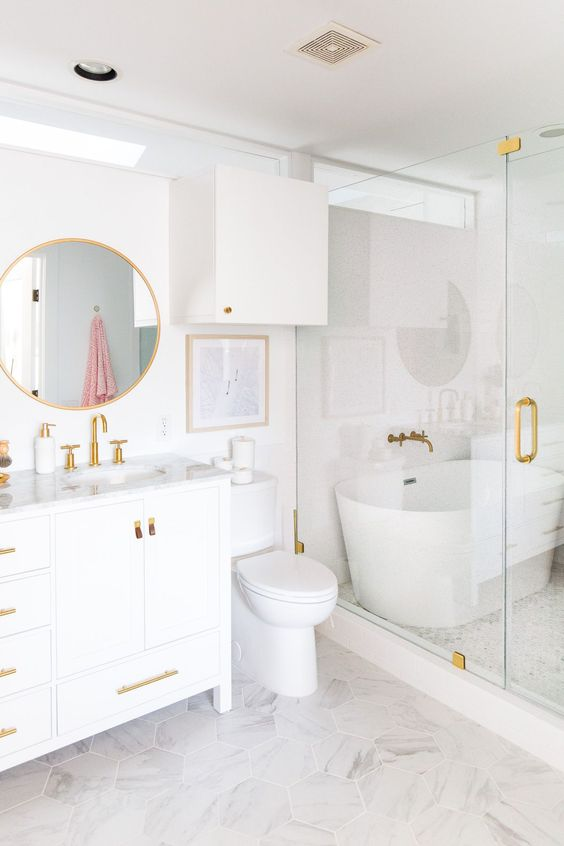 a refined bathroom with a vanity, white appliances and a shower space, gold fixtures and other touches for a more chic look