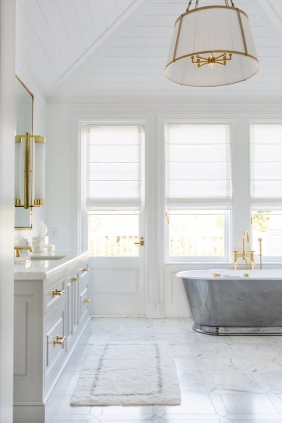 a refined coastal bathroom with a marble floor, a metal clad tub, a large vanity and gold touches and fixtures