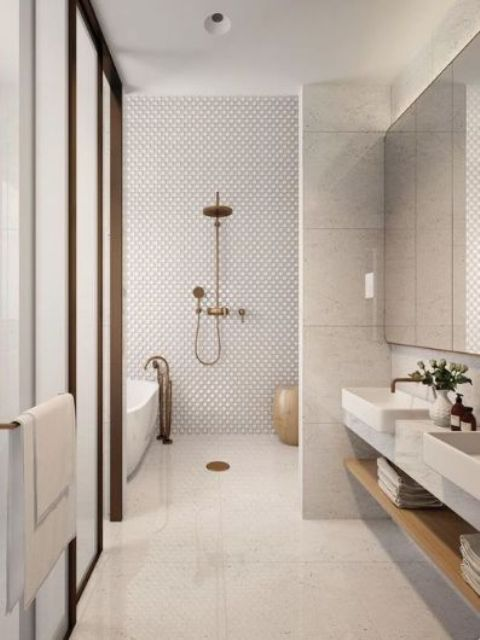 a refined contemporary bathroom with penny, large scale tiles, a floating vanity and a bathtub plus brass touches
