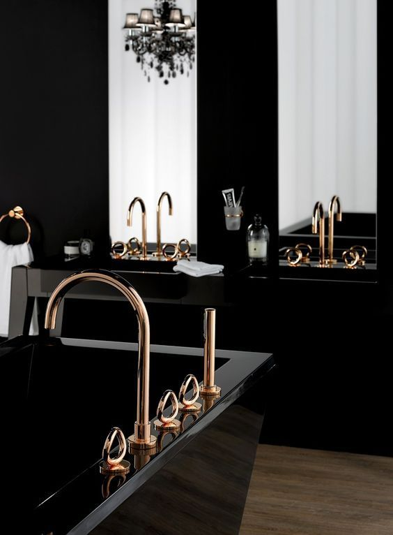 a refined modern Gothic bathroom with a black vanity and a polished tub, gold fixtures, tall mirrors and a black chandelier