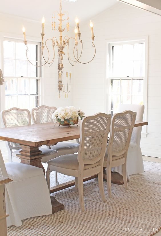 a refined neutral dining room with a stained table, whitewashed chairs with cane backs, a lovely chandelier and much natural light