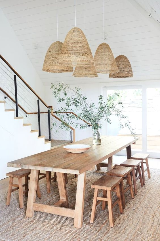 a relaxed boho rustic dining space with a stained dining set with stools, some pendant lamps and greenery on the table